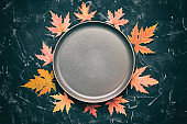 Autumn modern minimal composition. Empty plate and frame made of red dry maple leaves on a black stone background, toned. Top view, flat lay, copy space.Thanksgiving Day.