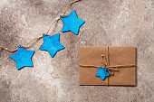 Craft envelope and wooden blue stars garland on a beige rustic background. Letter to Santa Claus. Beautiful Christmas and New Year card. Top view, flat lay.