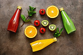 Assorted colored juices in bottles - tomato, orange, kiwi with fruits and mint leaves on a dark background. Top view, flat lay