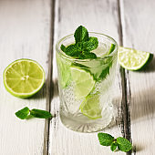 Refreshing cold drink with lime and mint in a glass on a white wooden board table. Traditional summer mojito cocktail. Selective focus, copy space
