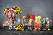 Colored lollipops, colorful round candies and marmalade in glass jars on a black stone table with a gray backdrop. Selective focus. Festive background with sweets.