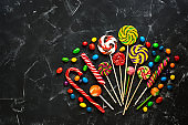 Colorful lollipops and colored round candies on a black stone background. Sweet celebratory background. Top view, flat lay,copy space.