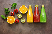Assorted colored juices - tomato, orange, kiwi with fruits and mint leaves on a dark background. Top view, flat lay, copy space.