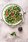 Salad figs, arugula and blue cheese in a white plate on a grunge beige background. Vegan and vegetarian lunch or dinner. Top view, flat lay, copy space.