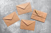 Brown craft envelopes on a gray concrete background. Top view, flat lay.