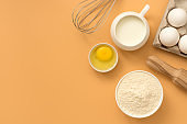 Baking Ingredient- flour, egg, milk, rolling pin, whisk on a pastel yellow background. Top view, flat lay, copy space.