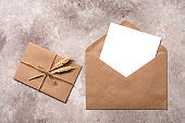 Blank paper card mockup in a craft brown envelope. Vintage letter tied with twine with ears of ripe wheat. Invitation template. Beige grunge background. Top view, flat lay.