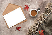 Autumn cozy composition, blank card with an envelope, a cup of coffee and a warm plaid. Blogger's desktop. Home Office. Top view, flat lay.
