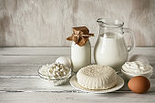 Fresh varied dairy products on a white wooden table. Side view, copy space.