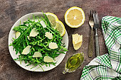 Light diet salad of arugula, parmesan and lemon on a dark rustic background. Top view, flat lay, copy space.