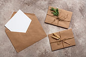 Blank card in craft envelope and vintage letters on on a beige grunge background. Modern minimal mockup. Top view, flat lay.