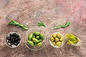 Assorted olives in glass bowls, olive oil and rosemary in a row on a dark background. Top view, flat lay, copy space.