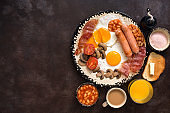 English traditional breakfast on a dark brown rustic background. Top view, flat lay, copy space. Fried eggs with bacon, sausages and beans, coffee, orange juice.
