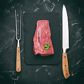 Raw fillet of beef on a slate plate, knife and fork for meat, black stone background. Top view, flat lay, toned.