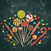 Colorful lollipops and colored round candies on a black stone background, toned. Festive sweet background. Top view, flat lay,copy space. Square photo.