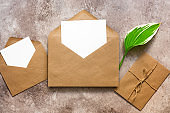 Blank cards mockup in envelope and green hosta leaf. Wedding invitation.Template for your design. Minimal stationery scene. Top view, flat lay, copy space.