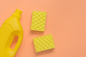 Flat lay yellow plastic bottle for liquid detergent, cleaning agent, antibacterial gel and washing sponge on pastel pink background. House cleaning concept. Top view.