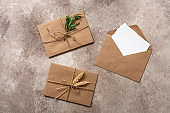 Blank greeting card, romantic letters in a craft envelope on a beige rustic background. Mock-up of invitation cards. Top view, flat lay.