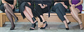 Stylish business women sitting in row next to each other on a wooden bench. Panoramic close-up legs and shoes.