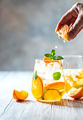 Homemade refreshing iced tea with orange and lemon on a wooden rustic table. Summer refreshing drink concept.