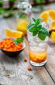 Sea buckthorn ice lemonade with oranges. Fruits and berries outdoors on a wooden table. Detox drinks.