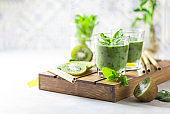 Detox green smoothie - kiwi, spinach and matcha on a light grey slate, stone or concrete background.