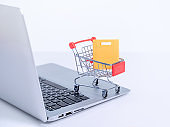 Online shopping. Mini shop cart trolley with colorful paper bags over a laptop computer on white table background.