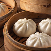 Delicious baozi, Chinese steamed meat bun is ready to eat on serving plate and steamer.