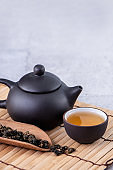 Hot tea in black teapot and cups and dry tea leaves over bright gray cement background.
