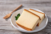 Castella (kasutera) - Delicious Japanese sliced sponge cake food on white plate over rustic wooden table.