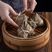 Rice dumpling, zongzi - Dragon Boat Festival, Bunch of Chinese traditional cooked food in steamer on wooden table over black background.