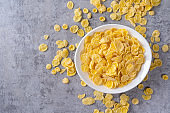 Corn flakes bowl sweets on gray cement background, top view flat lay layout design, fresh and healthy breakbast concept.