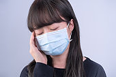 Young woman is feeling dizzy, headache, sick, unwell with wearing a medical blue face mask over the gray background.