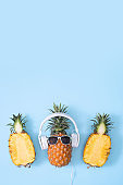 Funny pineapple wearing white headphone, concept of listening music, isolated on colored background with tropical palm leaves.
