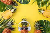 Funny pineapple wearing white headphone, listen music, isolated on yellow background with tropical palm leaves.