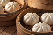 Delicious baozi, Chinese steamed meat bun is ready to eat on serving plate and steamer