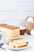 Castella (kasutera) - Beautiful delicious Japanese sliced sponge cake food on white plate over rustic white wooden table.