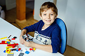 Little blond child playing with lots of colorful plastic blocks. Cute school kid boy having fun with building and creating robot. Creative leisure modern technic and robotic.