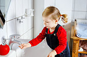 Cute little toddler girl washing hands with soap and water in bathroom. Adorable child learning cleaning body parts. Morning hygiene routine. Happy healthy kid at home or nursery.