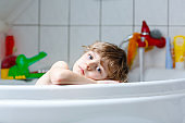 Cute little child playing with water by taking bath in bathtub at home. Adorable happy healthy preschool kid boy having fun, washing hairs and head and splashing with soap