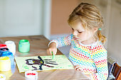 little creative toddler girl painting with finger colors an owl bird. Child having fun with drawing at home, in kindergarten or preschool daycare. Games, education and distance learning for kids.