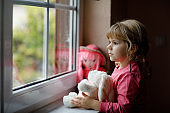 Cute toddler girl sitting by window and looking out on rainy day. Dreaming child with doll and soft toy feeling happy. Self isolation concept during corona virus pandemic time. Lonely kid.