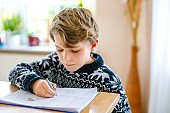 Hard-working happy school kid boy making homework during quarantine time from corona pandemic disease. Healthy child writing with pen, staying at home. Homeschooling concept