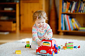 Little baby girl playing with educational wooden toys at home or nursery. Toddler with colorful red car. Child having fun with different toys. Lonely kid during corona virus pandemic quarantine