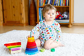 Adorable cute beautiful little baby girl playing with educational wooden toys at home or nursery. Toddler with colorful stack pyramid and music toy. Happy healthy child having fun with different toys