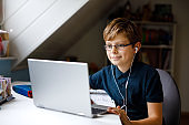 Kid boy with glasses learning at home on laptop for school. Adorable child making homework and using notebook and modern gadgets. Home schooling concept.