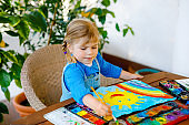 little toddler girl painting rainbow and sun with water colors during pandemic coronavirus quarantine disease. Children painting rainbows around the world with the words Let's all be well. Happy child