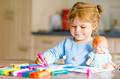 little alone toddler girl painting with felt pens during pandemic coronavirus quarantine disease. Happy creative child with old vintage doll, homeschooling and home daycare with parents
