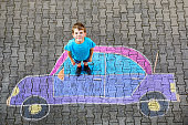 Adorable little kid boy playing with colorful chalks and painting big car picture on asphalt. Happy kid playing outside. Creative leisure for children outdoors in summer