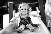 Cute toddler girl playing on slide on outdoor playground. Beautiful baby in colorful shorts trousers having fun on sunny warm summer day. Child sliding down